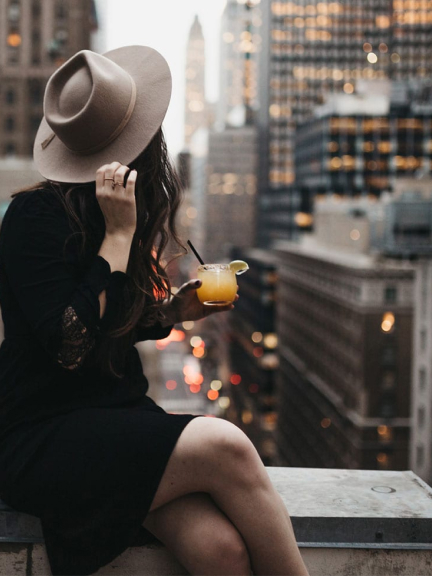 Woman with a drink overlooking NYC