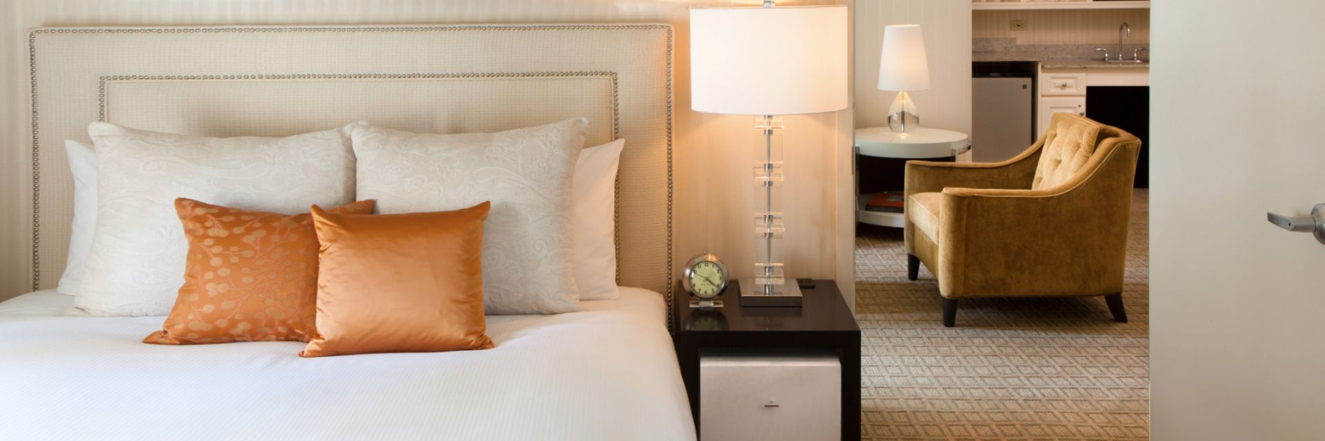 A bed overlooking a suite and kitchenette at The Benjamin