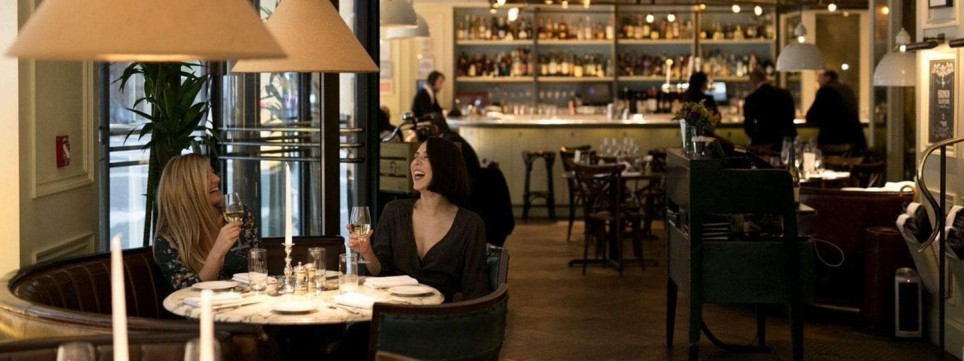 Two women laughing as they enjoy wine at their table in a restaurant.