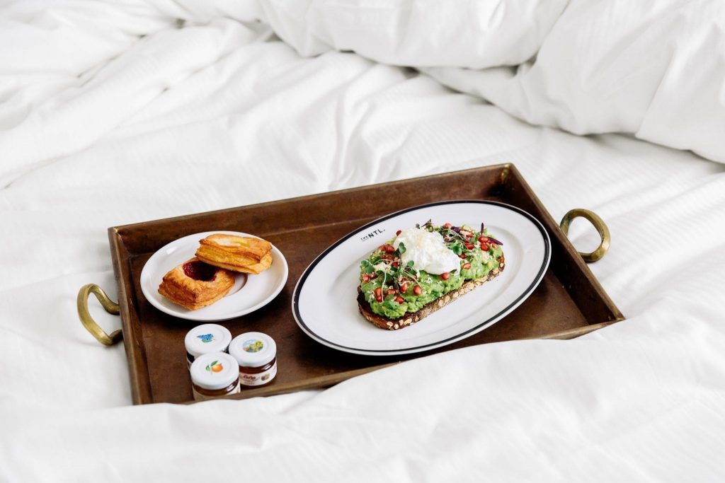 Tray of danish pastries, jam and avocado toast on a bed at The Benjamin Hotel