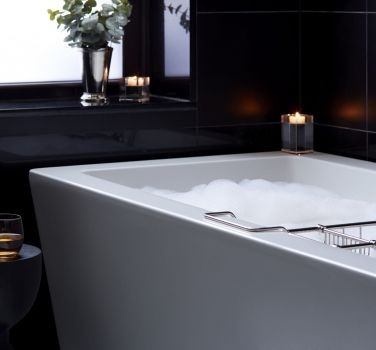 A crisp and clean bathtub filled with bubbles and surrounded by candles