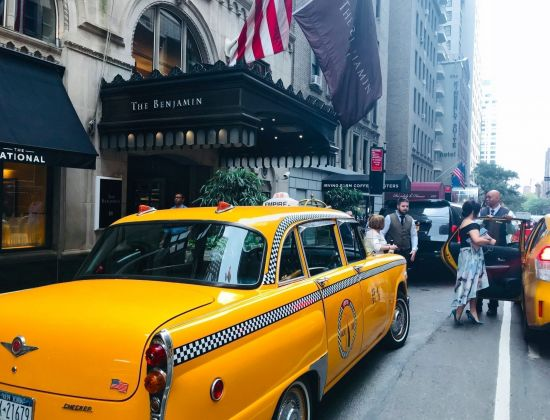 A yellow NYC cab outside The Benjamin Hotel
