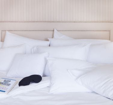 A fluffy white bed at The Benjamin Hotel in NYC