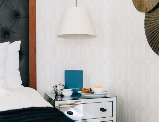 A light breakfast and tea on a bedside table at The Benjamin Hotel NYC