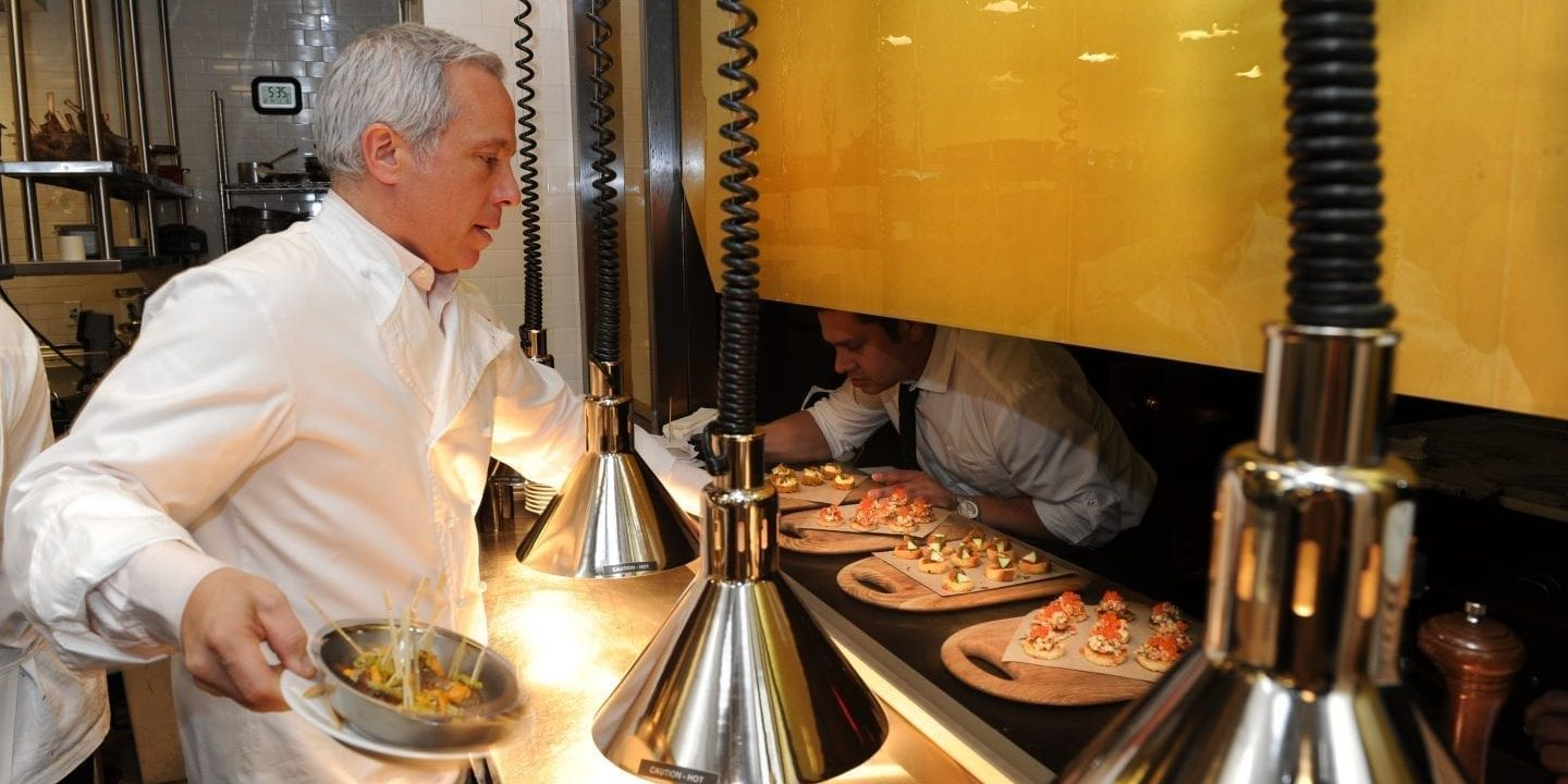 Chief Geoffrey Zakarian passing food to a server