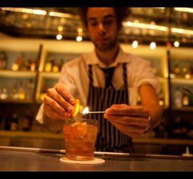 A mixologist preparing a drink at The National Bar in NYC