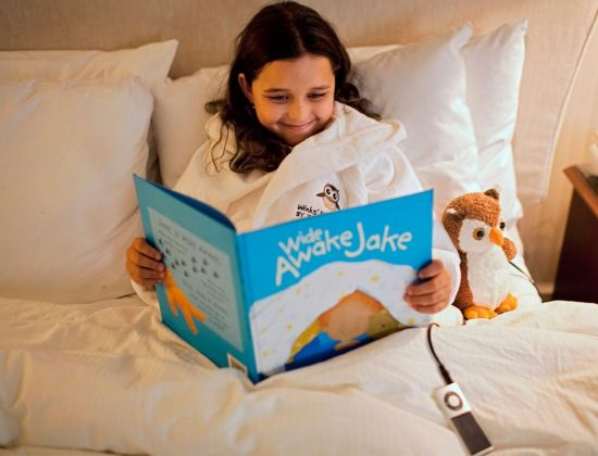 A girl tucked into bed reading Wide Awake Jack from the Winkzzz Kids Club at The Benjamin Hotel NYC