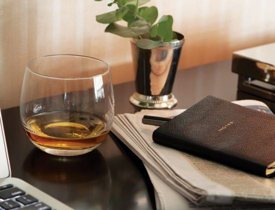 A glass of whisky and a leather notebook on a table at The Benjamin Hotel NYC